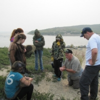 Roman Lamouelle (middle, in camouflaged jacket) learning about archaeological sites on the tundra from archaeologist Tom Andrews