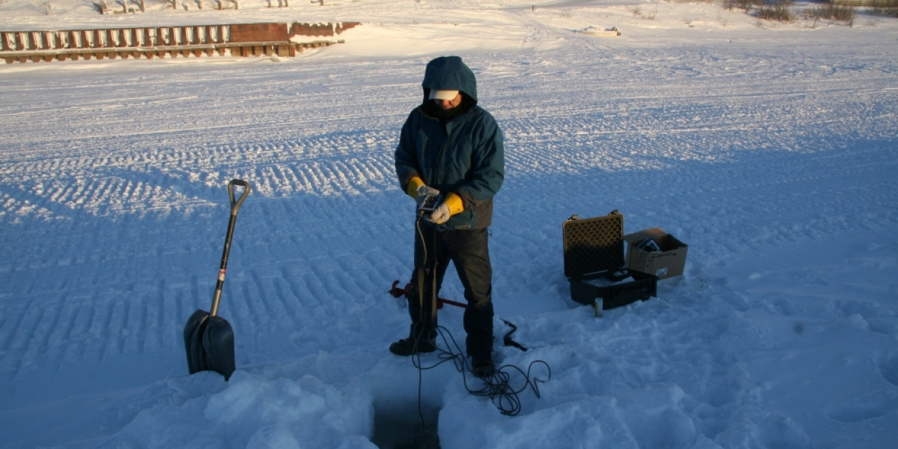 A technician from ARI takes a measurement of salinity and temperature at the water monitoring site at the Inuvik town dock